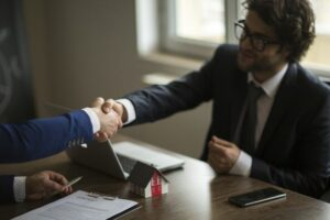 Two Men Shaking hands across a desk | Lease Genie offers new business equipment financing