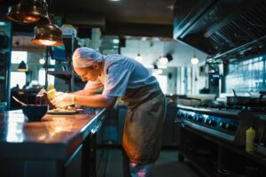 Cook working in a commercial kitchen | Lease Genie offers lease finance for restaurants.