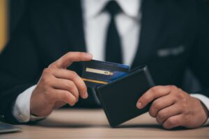 Man inserting a Credit card into a wallet | Lease Genie offers Lines of credit to businesses.